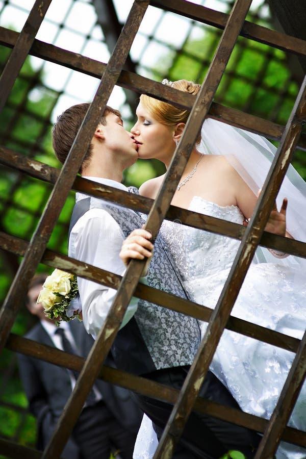Kiss the bride and groom at wedding walk stock photos