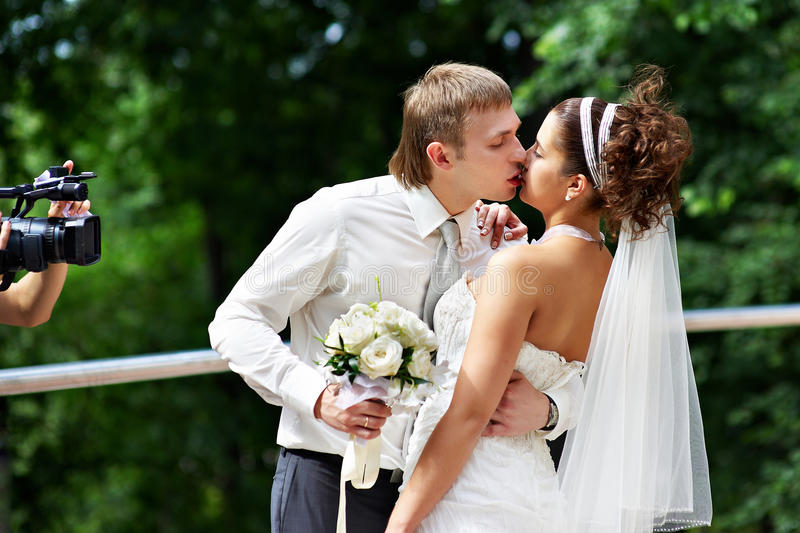 Kiss the bride and groom at wedding walk royalty free stock images