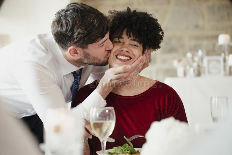 A Kiss On The Cheek At The Wedding Dinner. Wedding guests having fun at the meal. A women with an afro is getting a big kiss on the cheek by the groom on his stock image