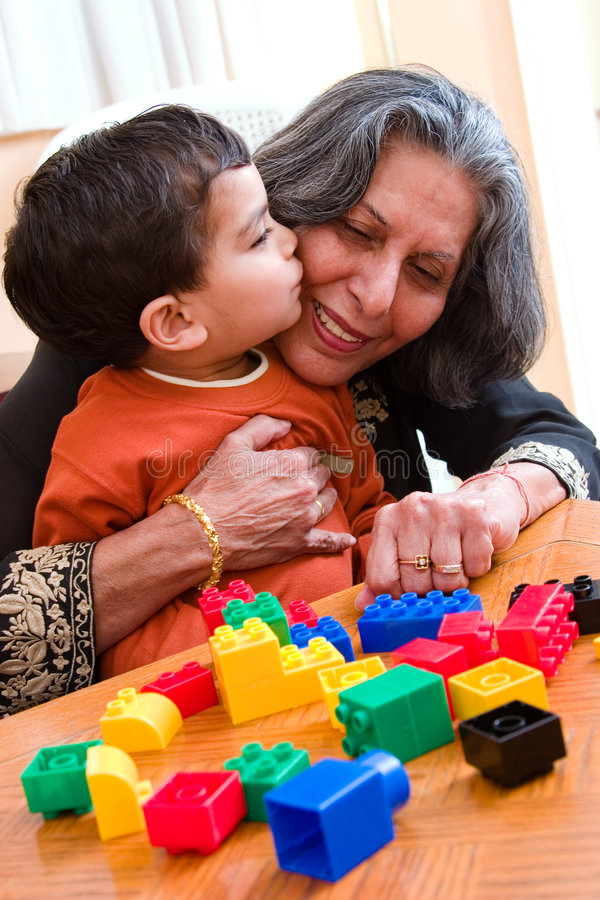 A kiss for Grandma. A child plays kisses his grandmother while playing with his toys stock images