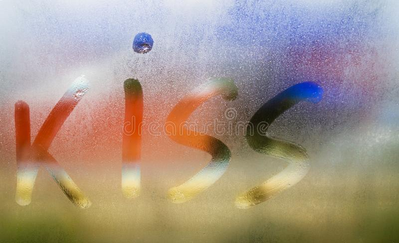 Kiss inscription painted on sweaty color glass on rain autumn day, Condensation and steam on window in cold autumn weather,. Kiss inscription painted on sweaty stock photography