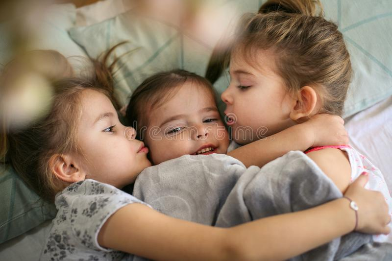 Kiss for little sister. Three little girls lying in bed and playing. Space for copy stock photo