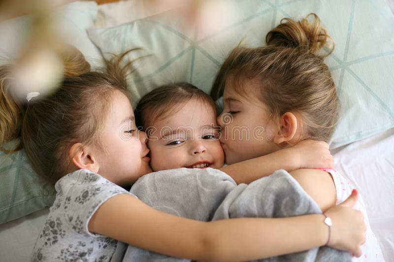 Kiss for little sister. Three little girls lying in bed and playing. Space for copy royalty free stock photos