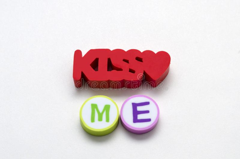 Kiss me phrase. Made from colorful erasers against white background royalty free stock photos
