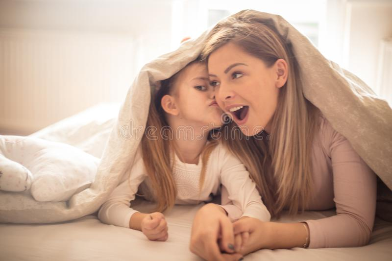 Kiss for mom. Mother and daughter playing in bed stock image