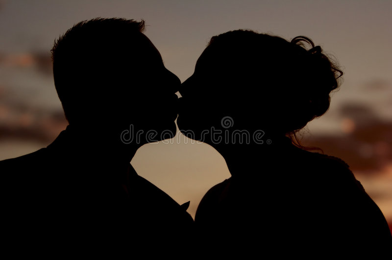 The kiss at sunset (silhouette) royalty free stock images