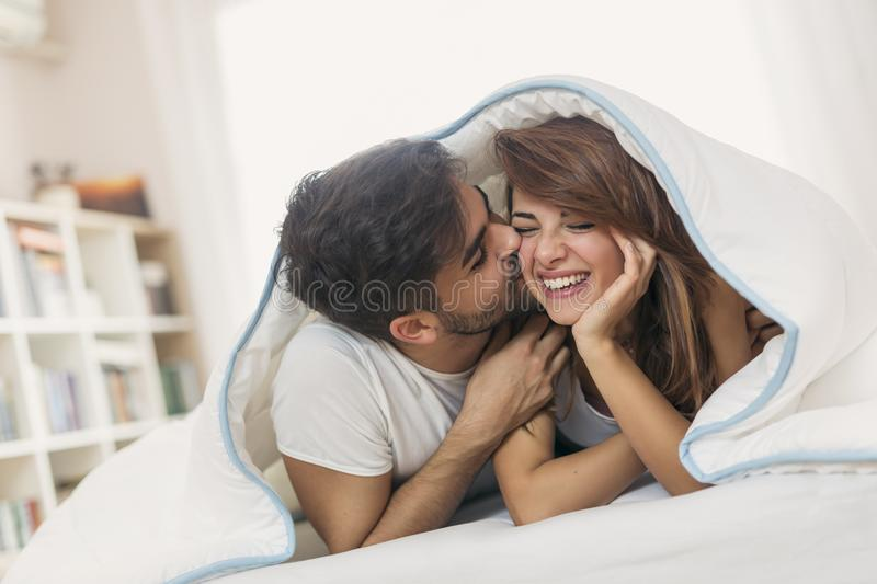 Kiss under the sheets. Couple in love lying under the sheets, kissing and laughing royalty free stock image