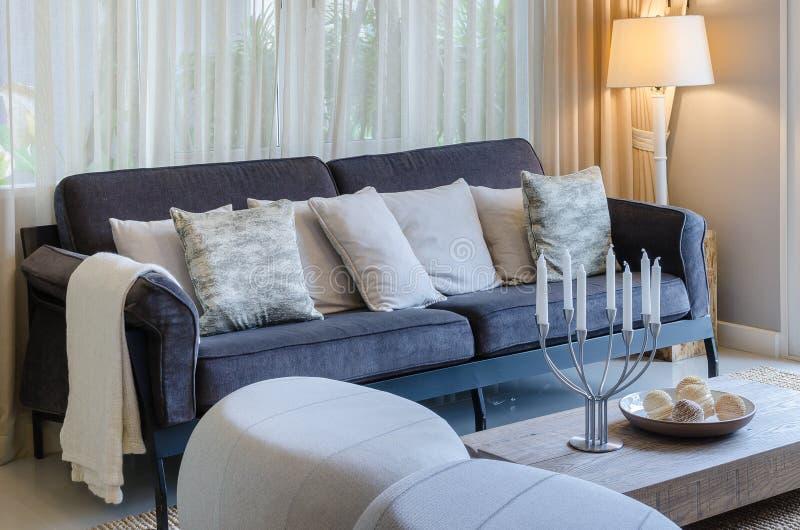 Kissen auf blauem Sofa mit Lampe und Kerzenhalter auf Holztisch stockfoto