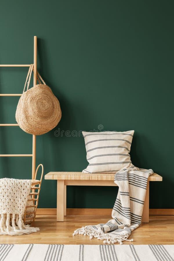 Kissen auf hölzernem Schemel nahe bei Tasche im grünen Wohnzimmer Innen mit Wolldecke Reales Foto lizenzfreie stockfotografie