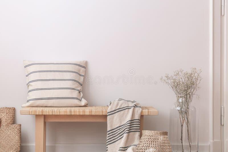 Kissen und Decke auf Holzbank nahe bei Blumen im beige minimalen flachen Innenraum Reales Foto lizenzfreie stockbilder
