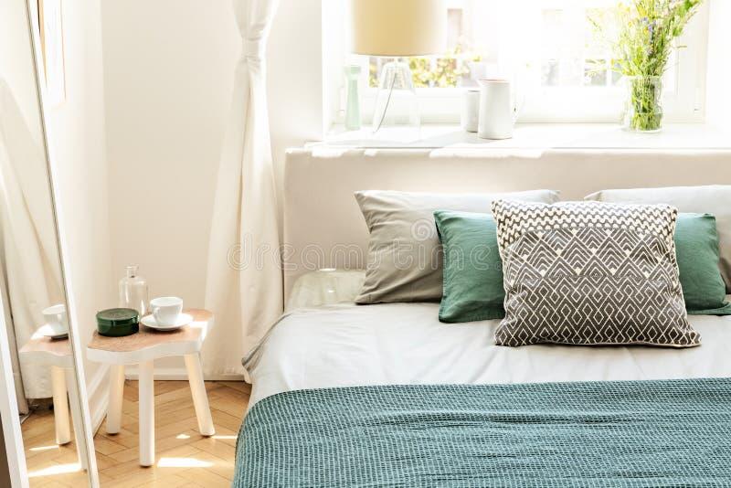 Kissen und grüne Blätter auf Bett im Schlafzimmerinnenraum mit weißem t lizenzfreie stockfotografie