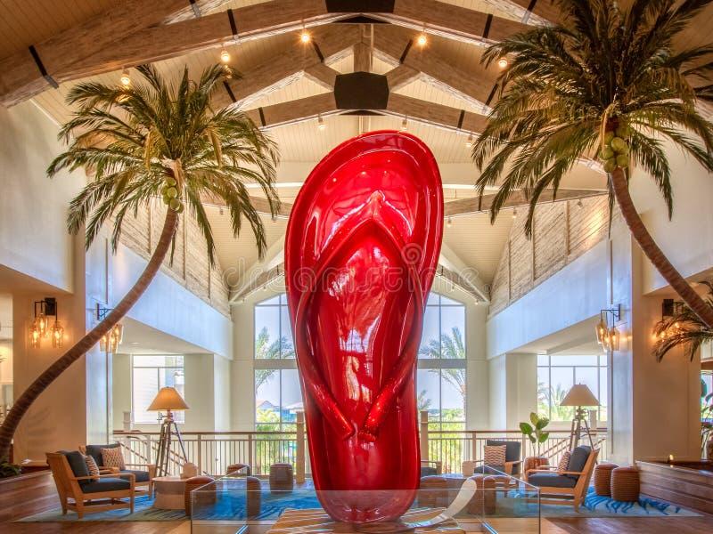 KISSIMMEE FLORIDA - MAJ 29, 2019 - Margaritaville semesterort Orlando Gigantiskt konstverk av en skinande röd sandal i det huvuds arkivfoto