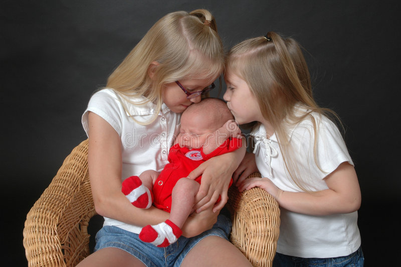 Kissing Baby Brother. Two young sisters on a black background holding and looking at their new baby brother royalty free stock image