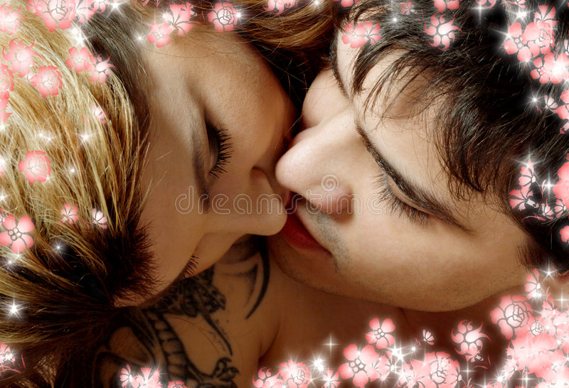 Kissing in bed with flowers stock photography