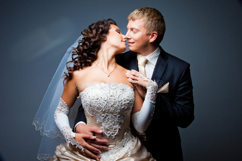Kissing bride and groom stock photography