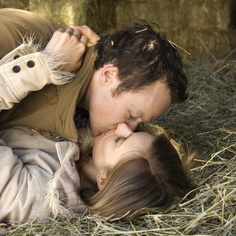 Kissing couple. Mid-adult Caucasian couple kissing and lying in hay stock photography