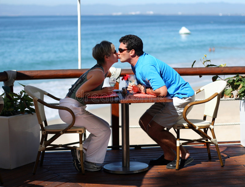 Kissing couple. At a seaside cafe