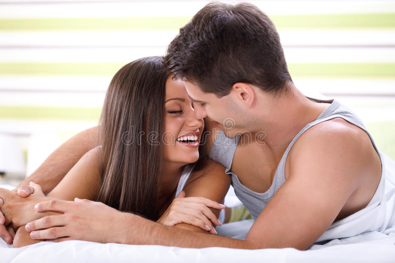 Kissing couple in bed royalty free stock image