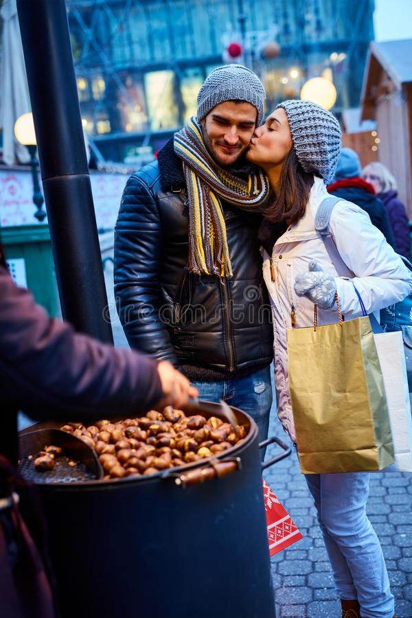 Kissing couple buying roasted chestnuts royalty free stock image