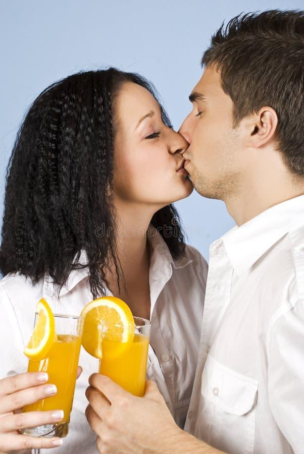 Kissing couple celebrate with fresh orange juice