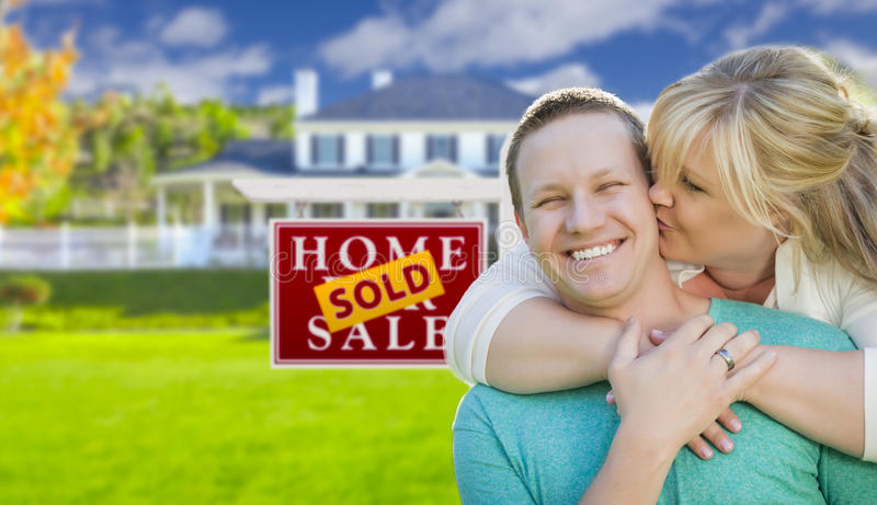Kissing Couple In Front Sold Real Estate Sign and House. Happy Couple Hug In Front of Sold Real Estate Sign and Beautiful New House stock photography