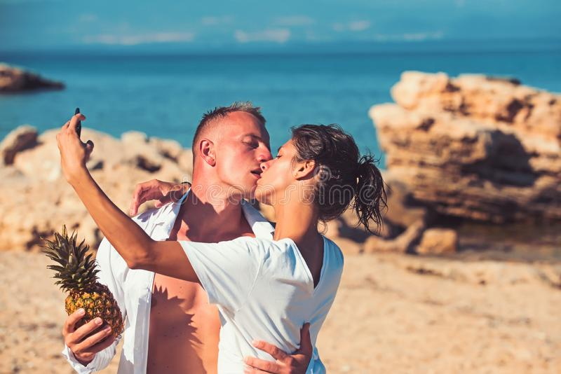 Kissing couple holding pineapple on the beach and makeing selfie. Kissing couple holding pineapple on the beach and makeing selfie royalty free stock image