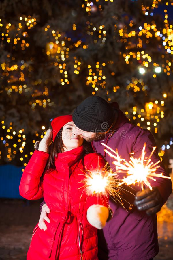 Kissing couple with sparkling bengal lights outdoors stock image