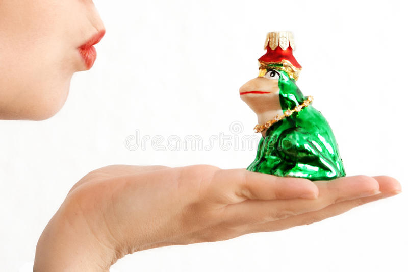 Kissing a frog. Frog (christmas ornament) on hand, symbolizing kissing a frog to find a prince stock photography