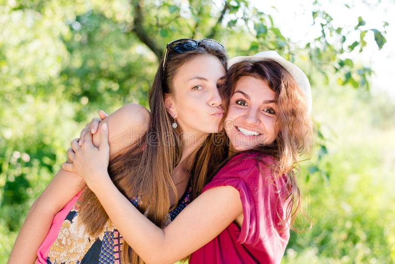 Kissing fun: brunette young women best friends having joyful time laughing & looking at camera on green su stock image