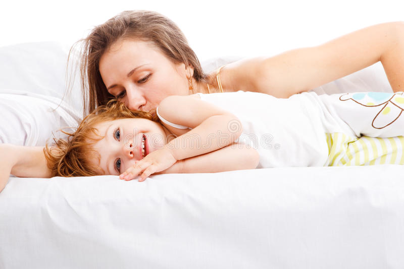 Kissing good night. Mother kissing good night to her lovely little daughter royalty free stock photography