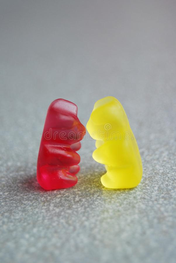 Kissing gummy bears, yellow and red, on a grey background, funny love. Two gummy bears yellow and red, standing up and kissing on a grey background, abstract and stock images