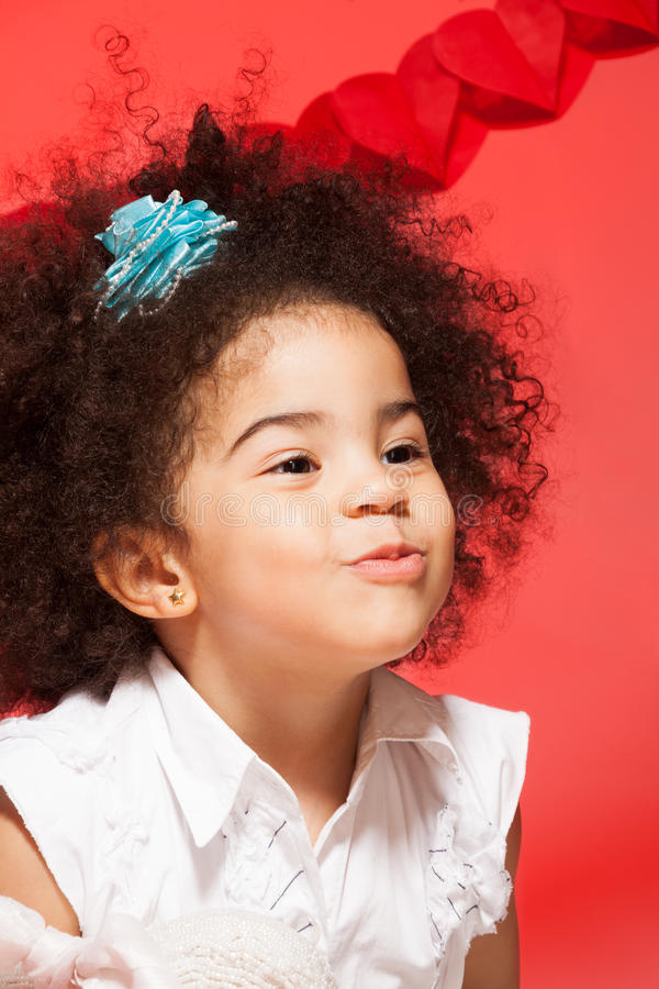Kissing little black curly girl. On red valentine day background royalty free stock photos