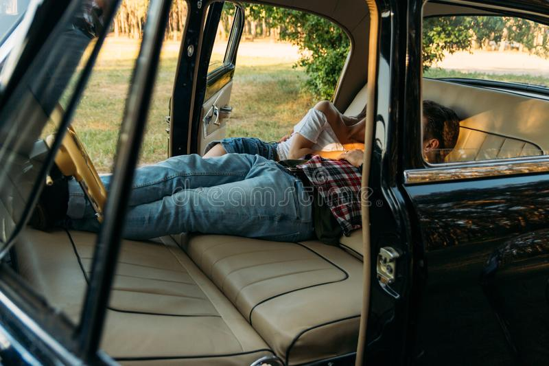 Kissing people who are lying in the car and holding hands. look through the window in the car.side view.dressed in a plaid shirt,. Shorts and jeans, a white stock image