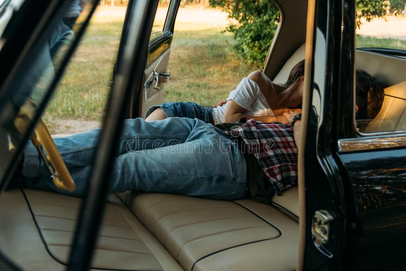 Date in the car.kissing people who are lying in the car and holding hands. look through the window in the car.side view.dressed in. Kissing people who are lying royalty free stock photography