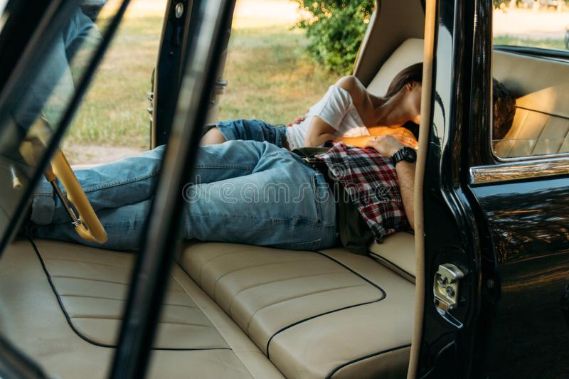 Kissing people who are lying in the car and holding hands. look through the window in the car.side view.dressed in a plaid shirt,. Shorts and jeans, a white royalty free stock photography