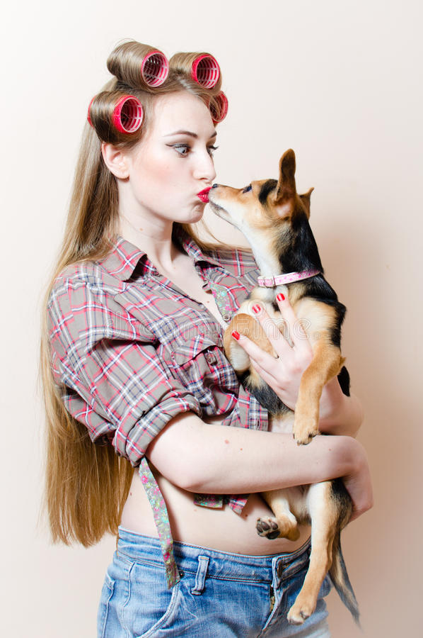 Kissing puppy: beautiful blond young woman pin up girl with curlers on her head having fun with little funny dog stock photo