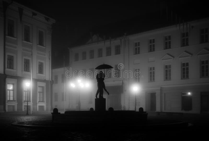 Tartu town hall square on a foggy night. Kissing Students fountain in Tartu Town Hall square on a foggy autumn night. Estonia, 2019 royalty free stock photography
