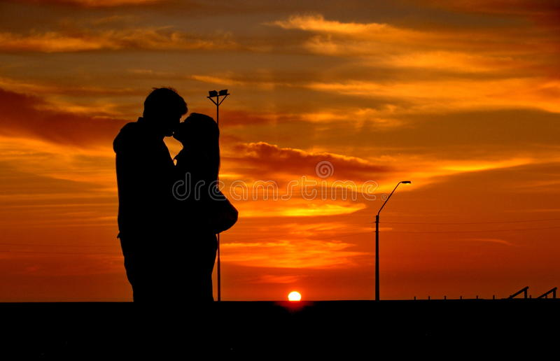Kissing at sunset stock photography