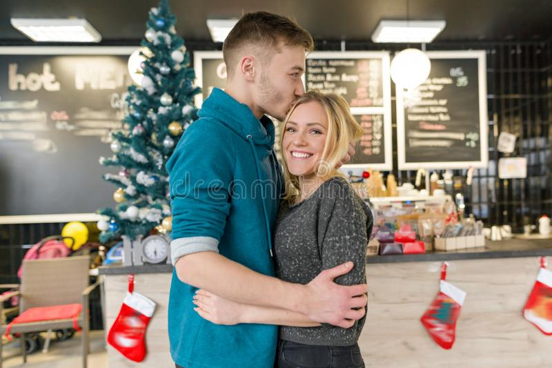 Kissing young couple near Christmas tree in cafe.  stock photography
