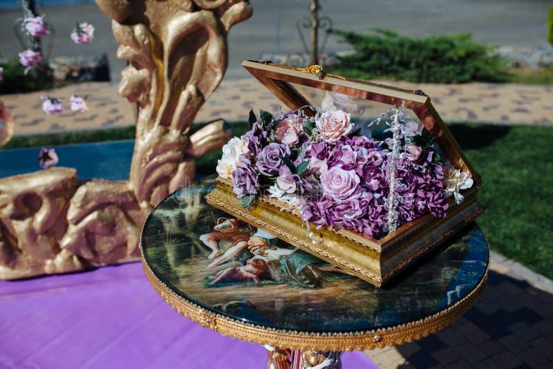 Kist met purpere bloem op het decor van de Huwelijksceremonie met gouden luxekader op lijst Bruid en bruidegomceremonie royalty-vrije stock foto