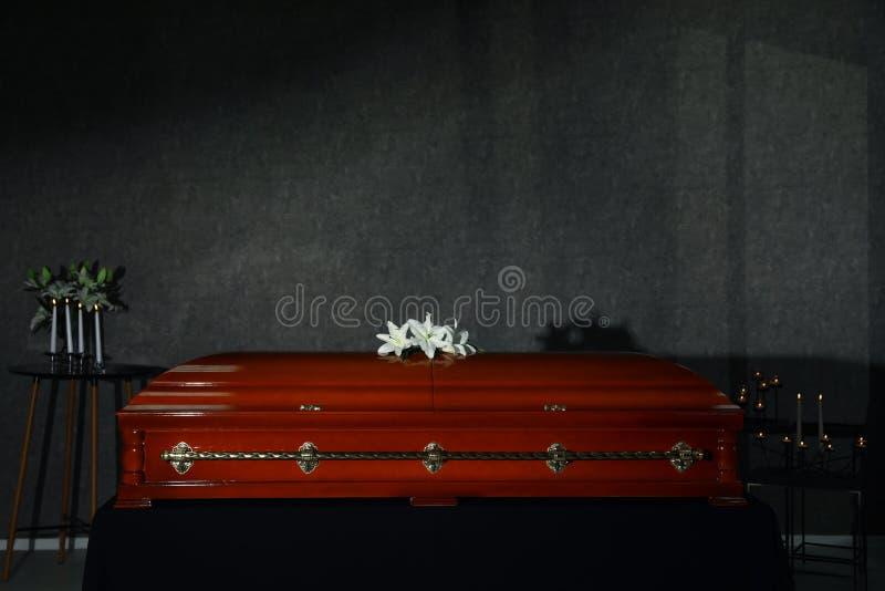 Kist met witte lelies en brandende kaarsen in rouwkamer royalty-vrije stock afbeelding