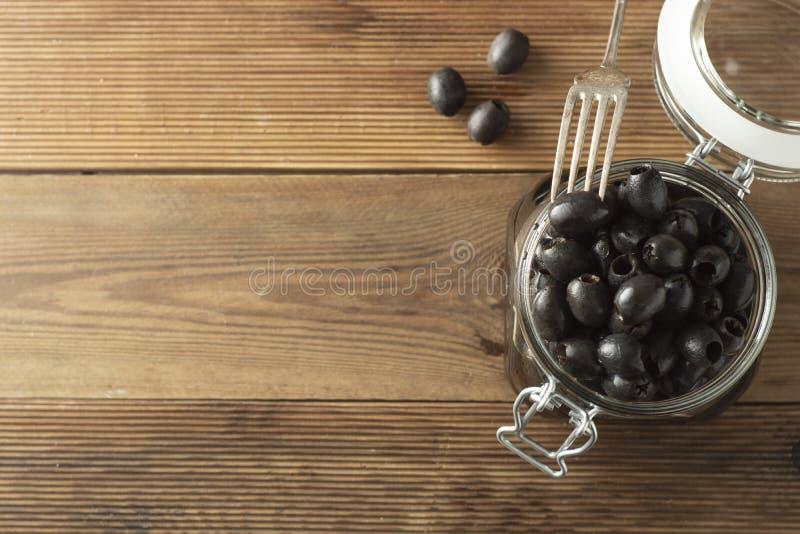 Kiszone do?kowate czarne oliwki w szklanym s?oju, drewniany t?o Mediteranian foods kosmos kopii fotografia royalty free