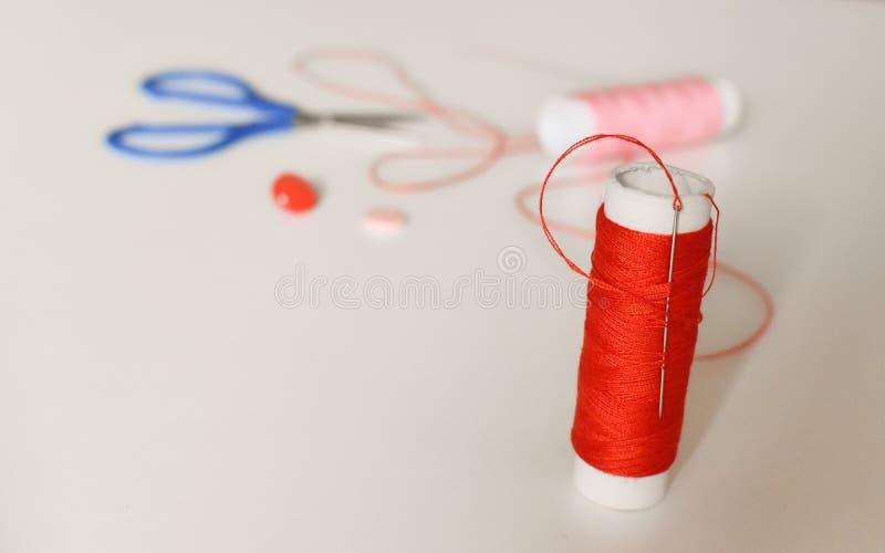 Kit de couture - aiguille coincée en fil rouge et dans les ciseaux et les boutons de fond photo libre de droits