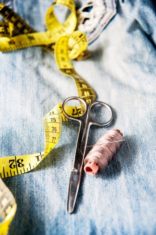Kit de couture des fils, des ciseaux et d'aiguille sur le backround de jeans images stock