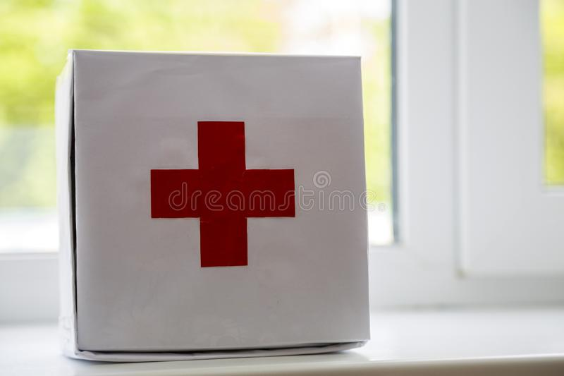 Kit de primeiros socorros branco com cruz vermelha dentro na soleira no fundo borrado Conceito dos cuidados m?dicos imagens de stock royalty free