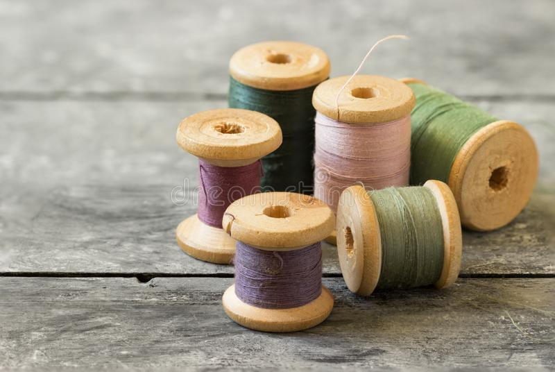 Kit di cucito Bobine del filo colorato sulla vecchia tavola di legno fotografia stock