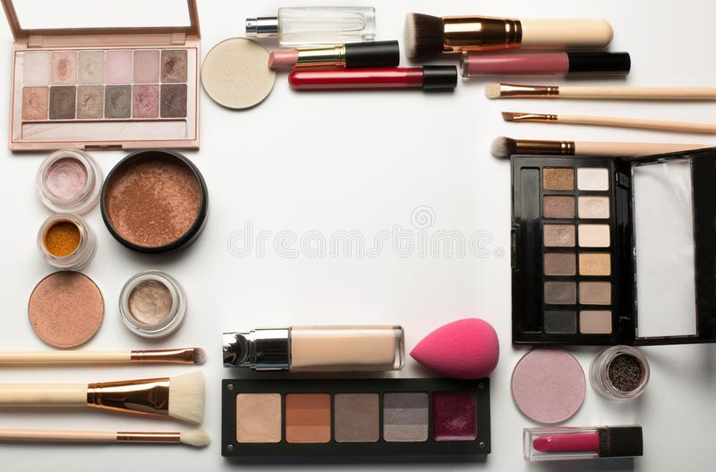 Kit of eyeshadow palettes, eye pigment and makeup brushes on a w. Set of professional eyeshadow palettes, makeup foundation and bronzer on a white background royalty free stock image