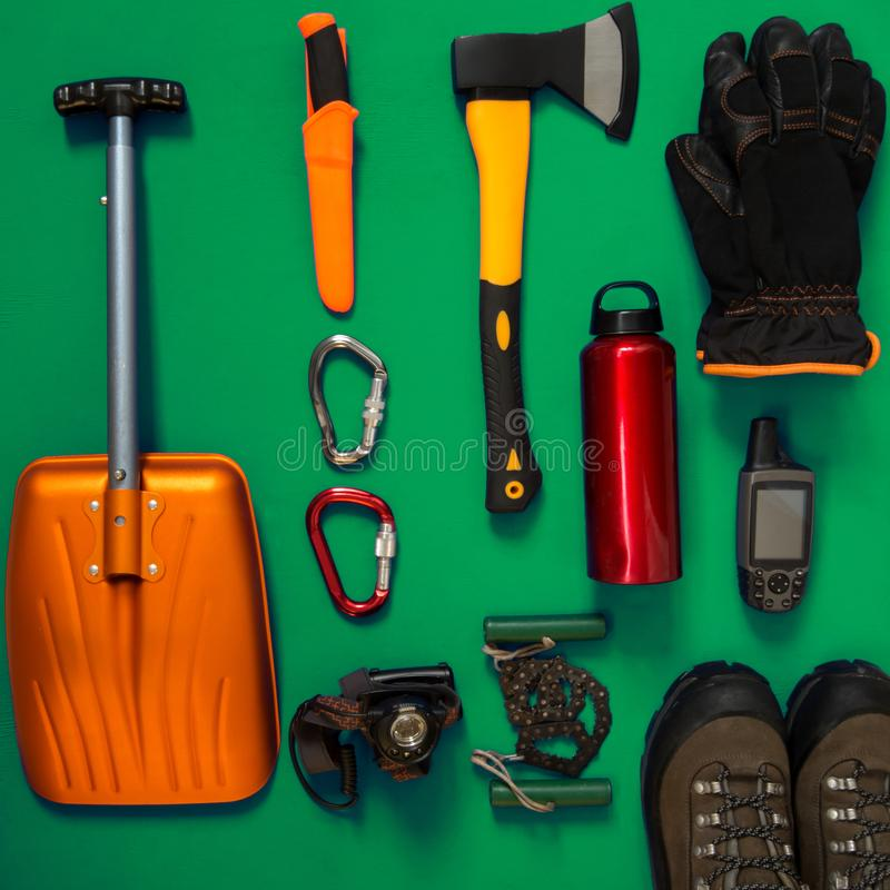 Kit of gear for survival on a green background. Kit of gear for hiking, adventure and survival in wilderness during winter - ax, avalanche shovel, gloves, gps stock photos