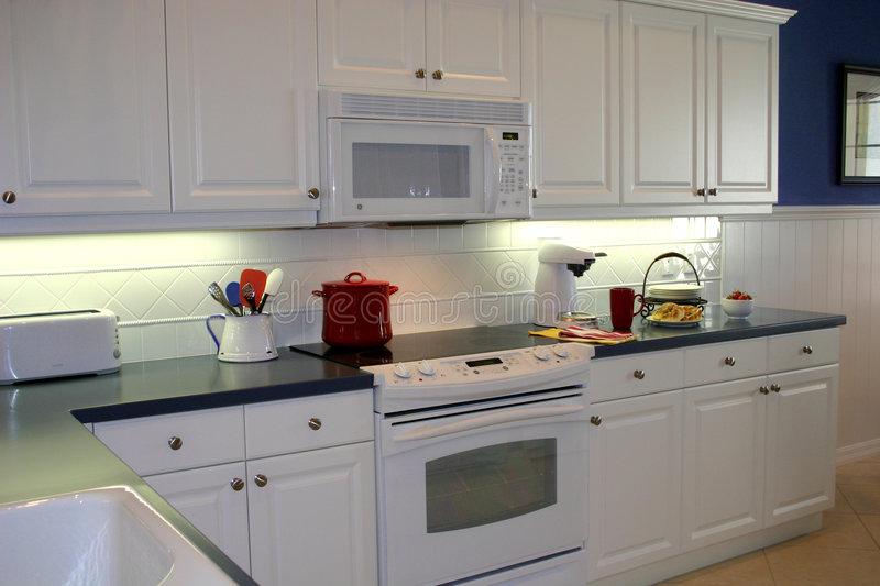 Kitchen. Pristine, immaculate, white kitchen with dark countertops and white electrical appliances