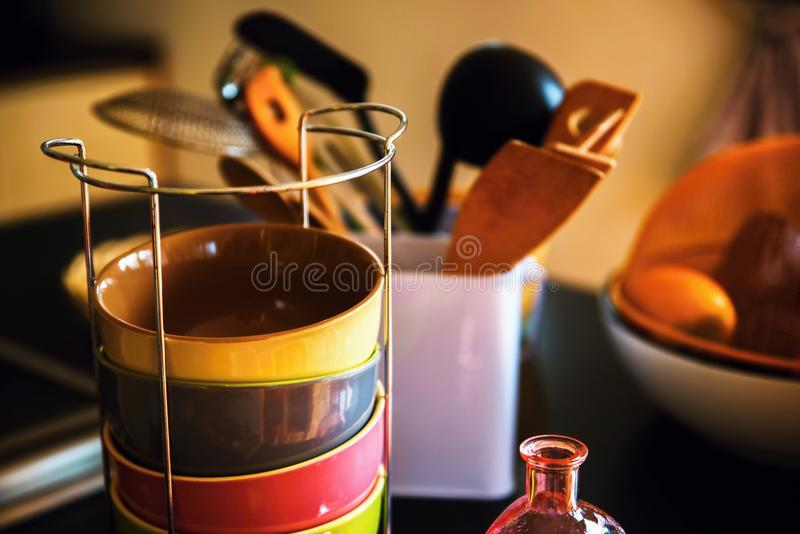 Kitchen accessoires on table. Accessoires what you need to cook in modern kitchen - colorful ceramic bowls, ladle, wooden spoon, glass and fruit in basket stock image